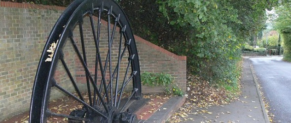 Picture shows a colliery winding wheel cut in half and fixed in the ground